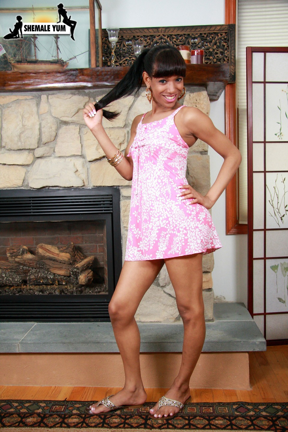 melody melendez posing by the fireplace in pink skirt